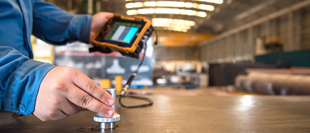 what is non-destructive testing - man using NDT on steel